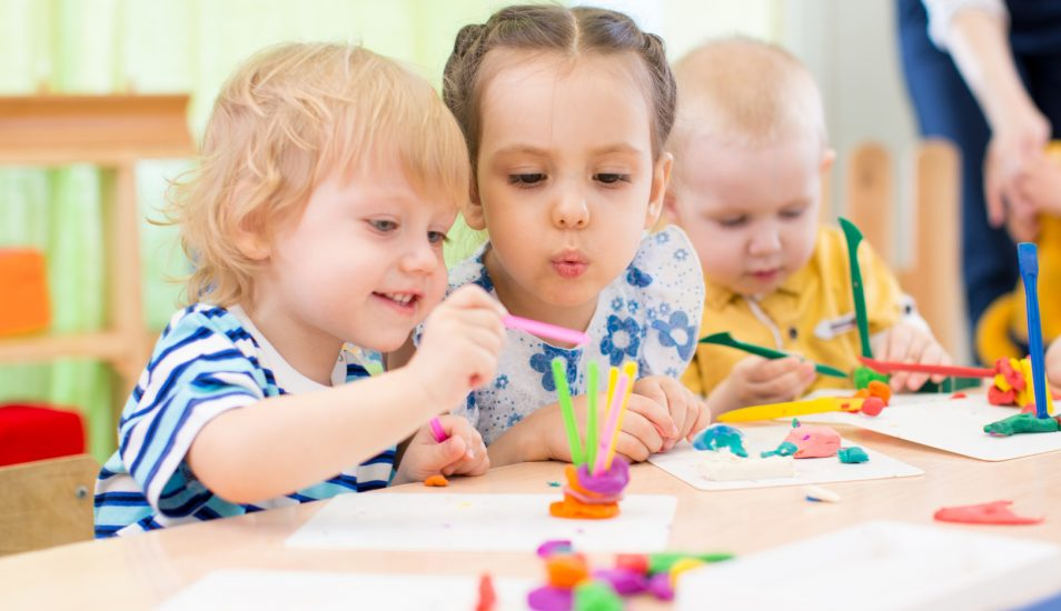 happy kids modeling or playing in kindergarten with interest