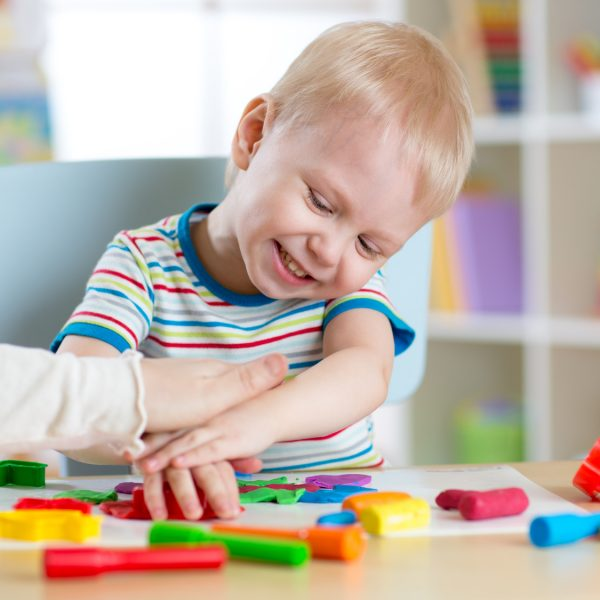 Child little boy playing with clay dough, education and daycare concept